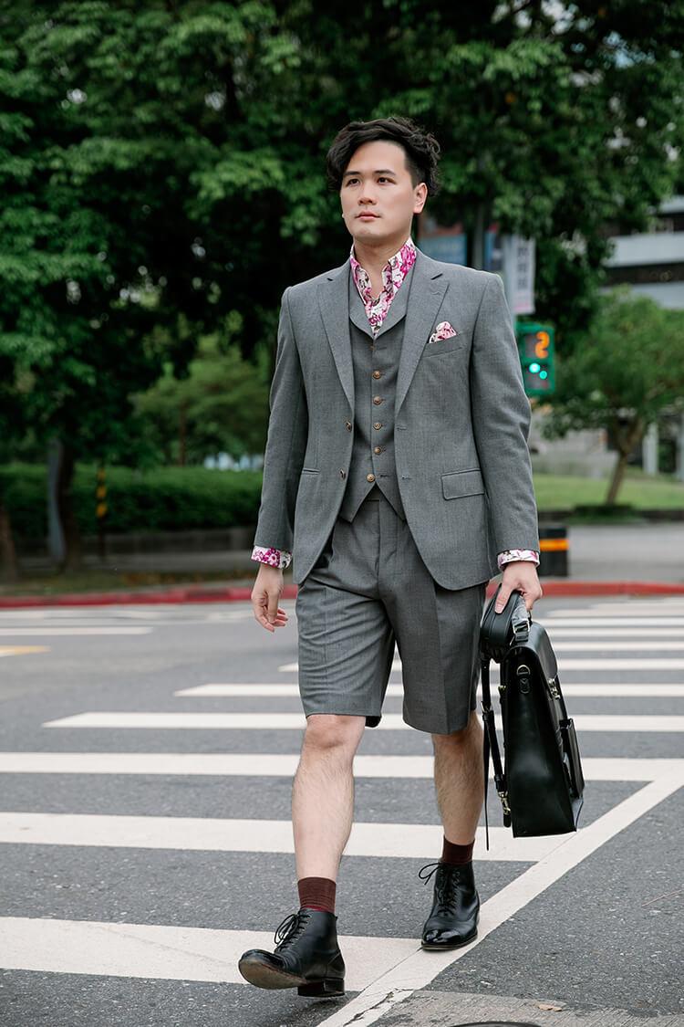 穿著灰色西裝與黑色靴子正在過馬路的男人