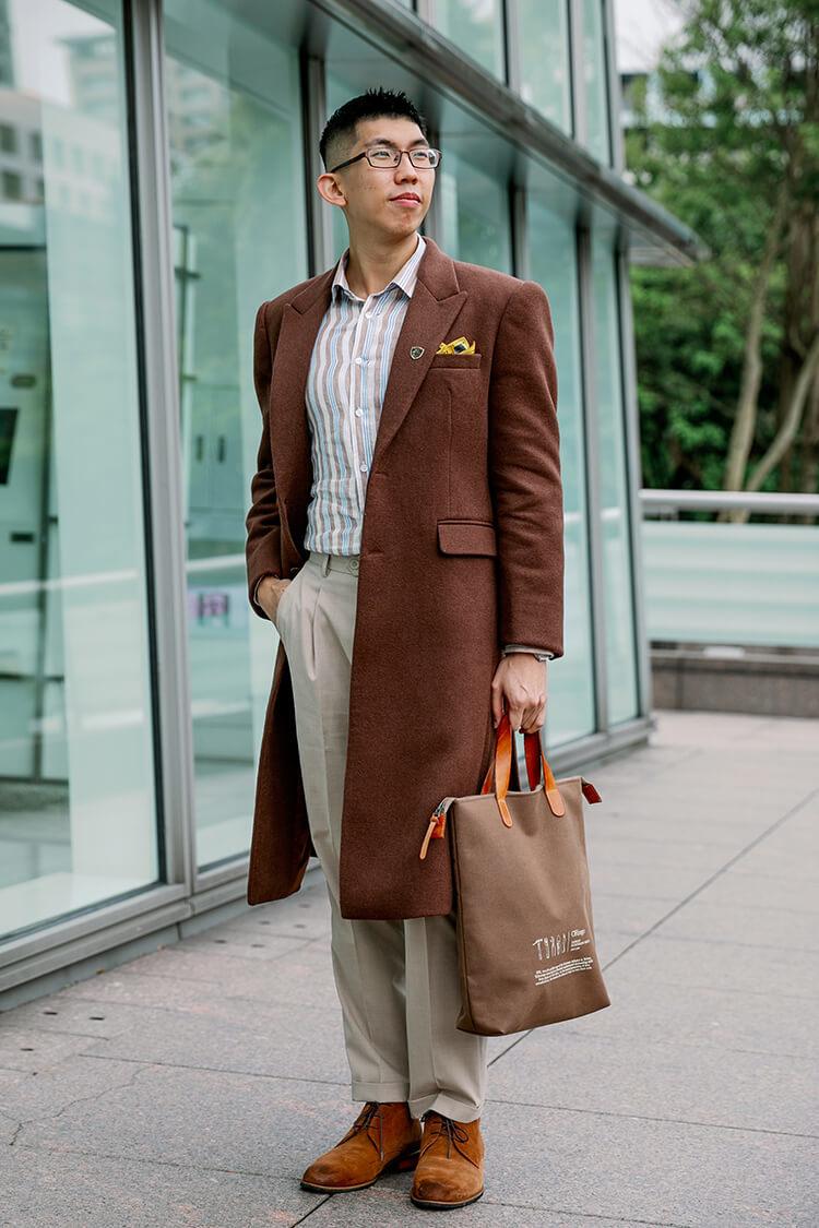 穿著咖啡色西裝外套與米色褲子跟咖啡色靴子的男人
