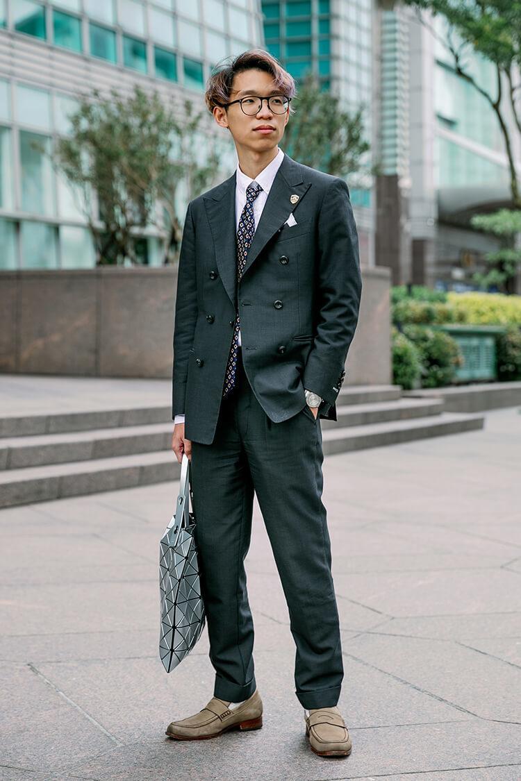 穿著黑色西裝與灰色樂福鞋的男人