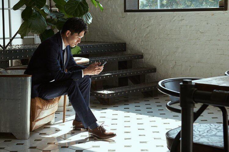 穿藍色西裝與咖啡色牛津鞋在玩手機的男人