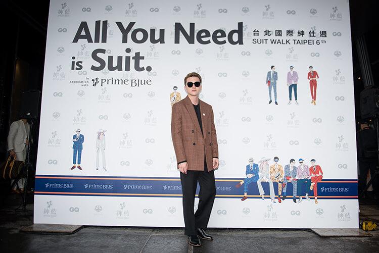 穿咖色西裝外套與黑色褲子鞋子且戴墨鏡的男人