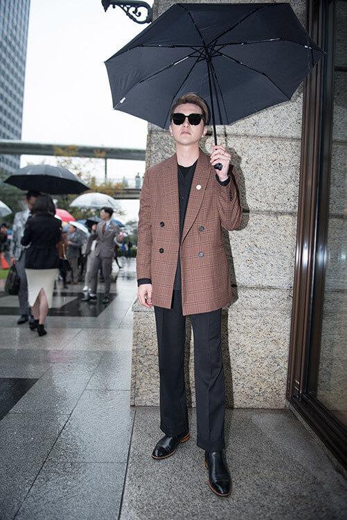 穿咖色西裝外套與黑色褲子鞋子且戴墨鏡的男人正在撐傘