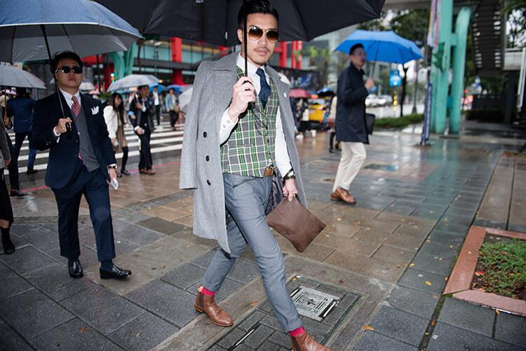穿灰色西裝與咖啡色雀爾喜且戴墨鏡的男人正在撐傘過馬路