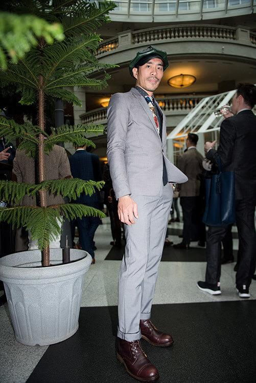 穿灰色西裝與咖啡色靴子且戴皮帽的男人