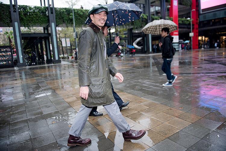 穿油布外套與灰色西裝與咖啡色靴子且戴皮帽的男人正在走路