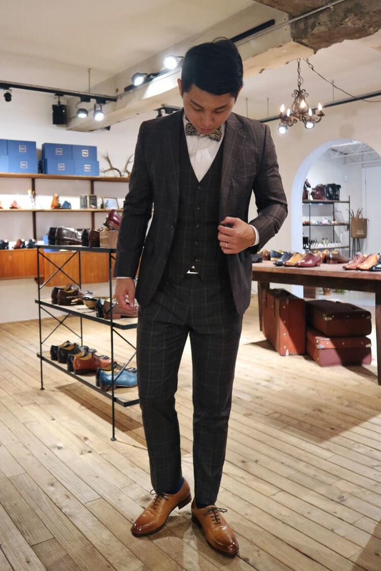 穿著鐵灰格紋西服與蜜棕色牛津鞋的男人
