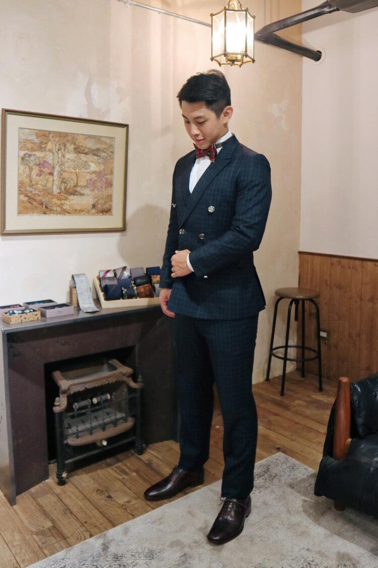 穿著藍色格紋西服與黑色牛津鞋的男人