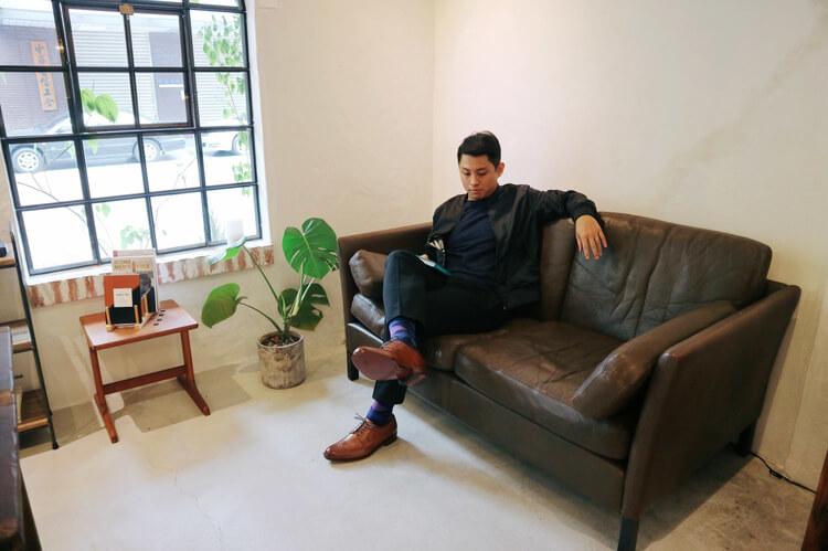 穿著深色西裝與咖啡色得比鞋坐在沙發上的男人