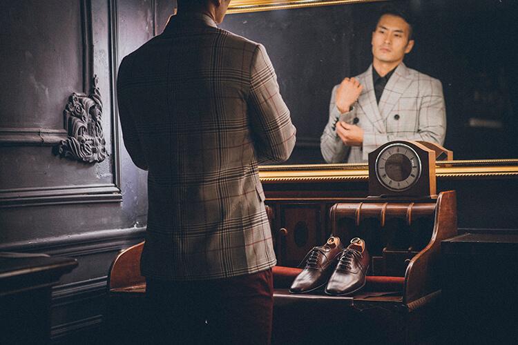 穿灰色西裝正在照鏡子的男人