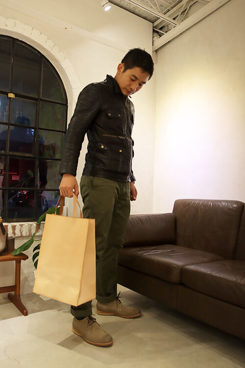 穿皮衣的男人提著皮革拖特包