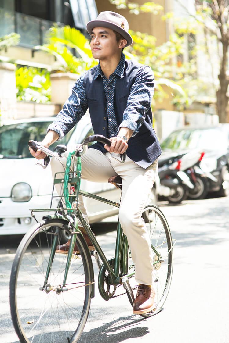 騎著腳踏車穿著藍色襯衫與白色褲子的男人