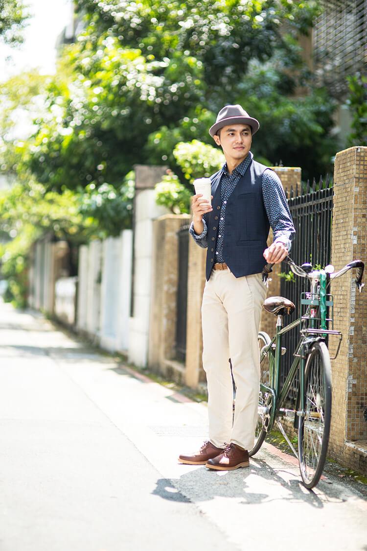 穿著藍色襯衫與白色褲子的男人正拿著咖啡扶著腳踏車