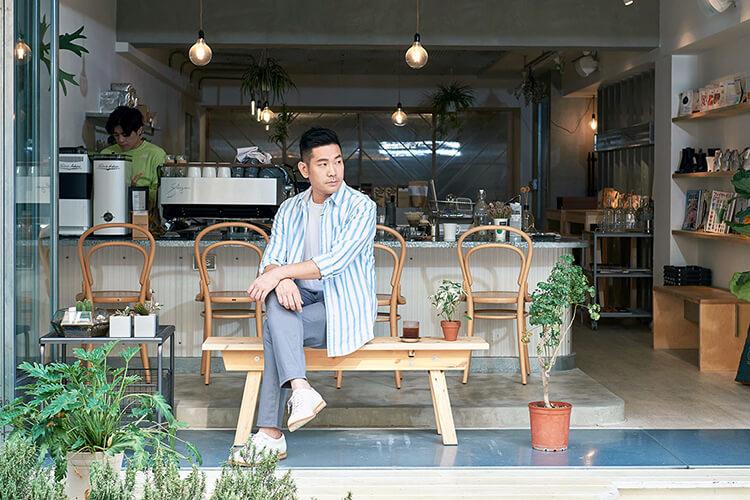 穿著白藍色襯衫與白色鞋子坐在椅子上的男人