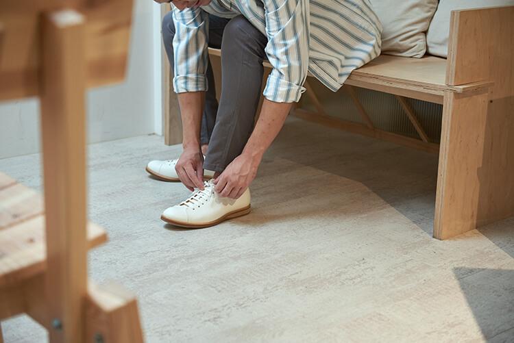 在在綁白色鞋子鞋帶的男人