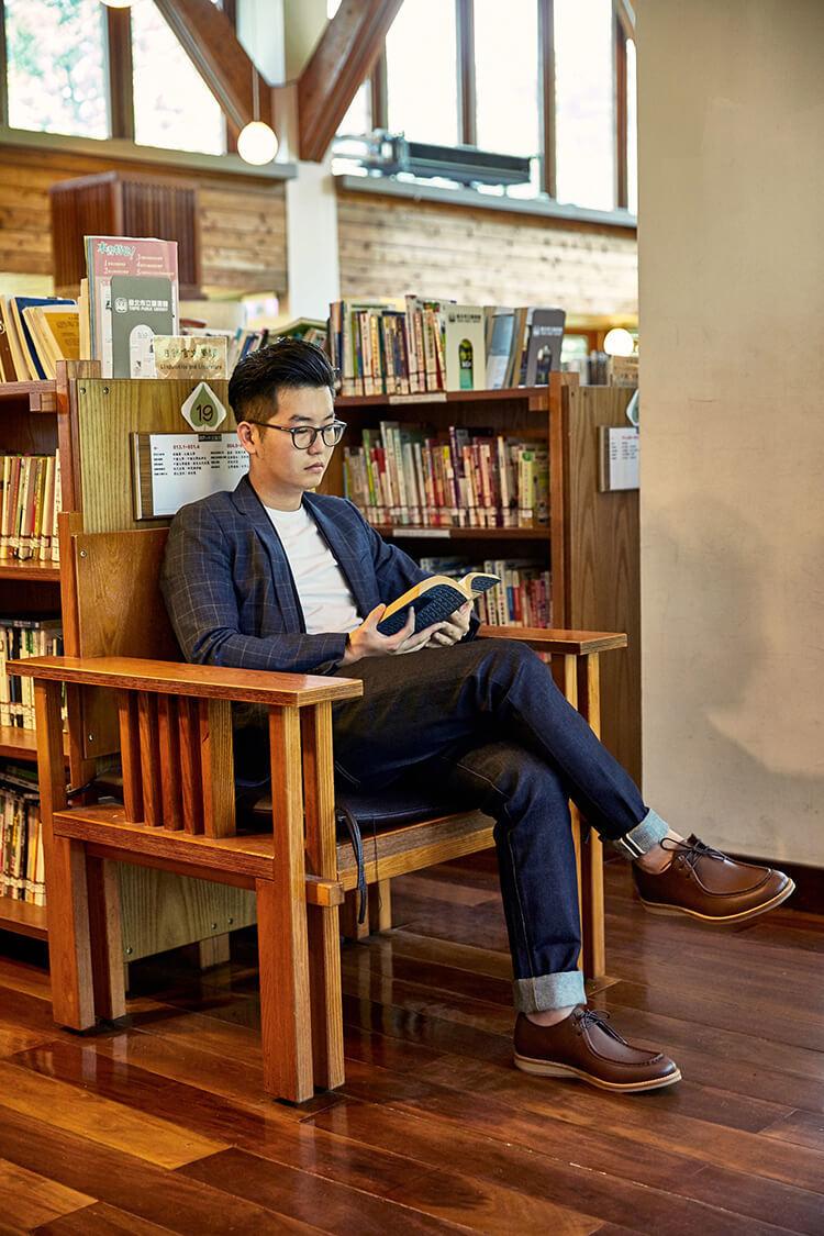 穿藍色西裝與深咖啡色袋鼠鞋正在看書的男人