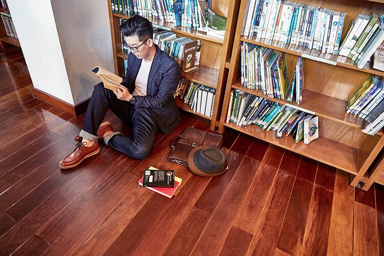 穿藍色西裝與磚色袋鼠鞋坐在地上看書的男人