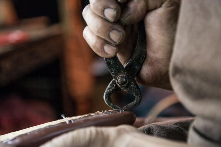 師傅將中底固定鞋面的釘子拔起