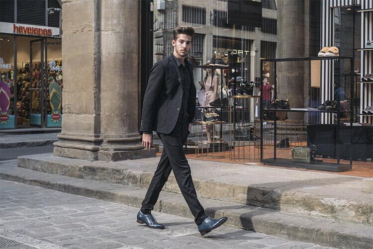一位穿黑西裝的歐美男人與藍色牛津鞋