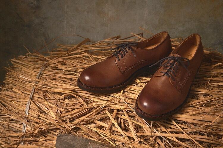 放在稻草上的咖色德比工作鞋