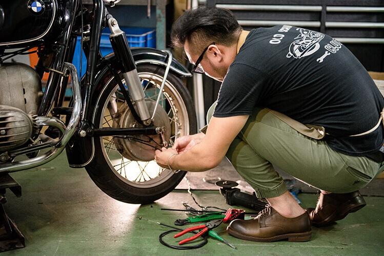 一名男人穿著工作鞋在修理機車