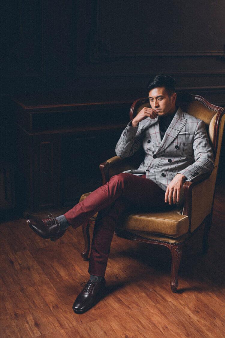 穿灰西裝外套配紅色褲子與酒紅牛津鞋的男人坐在沙發上