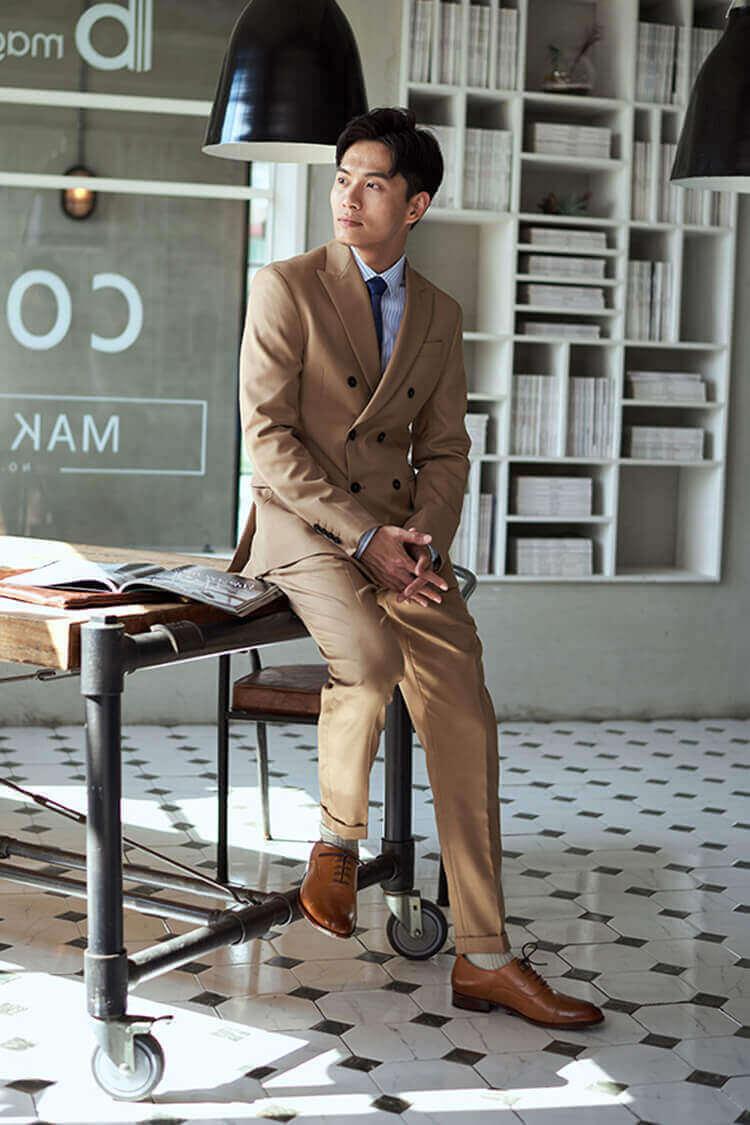 一名穿卡其色西裝與棕色牛津鞋的男人