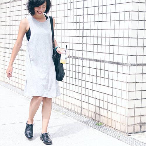 一名女人穿著無袖洋裝與黑色牛津鞋