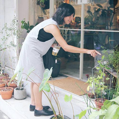 一名女人穿著洋裝與牛津鞋手指植物