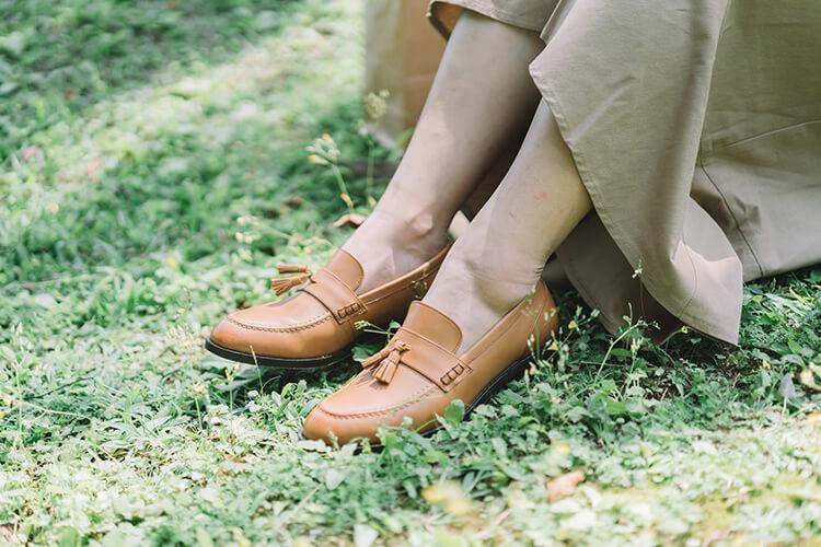 一名女人穿著長裙與棕色樂福鞋坐在草地上