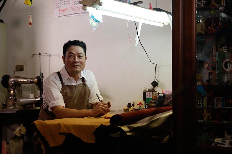 一名男人穿著圍裙坐在桌前