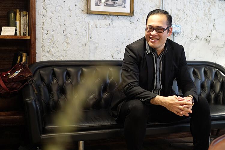 林果客人李寬敏穿著黑西裝坐在沙發上笑得燦爛