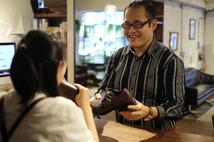 林果客人李寬敏拿著鞋在櫃檯前與店員相談甚歡