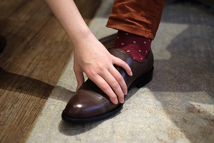 一隻手在碰觸皮鞋