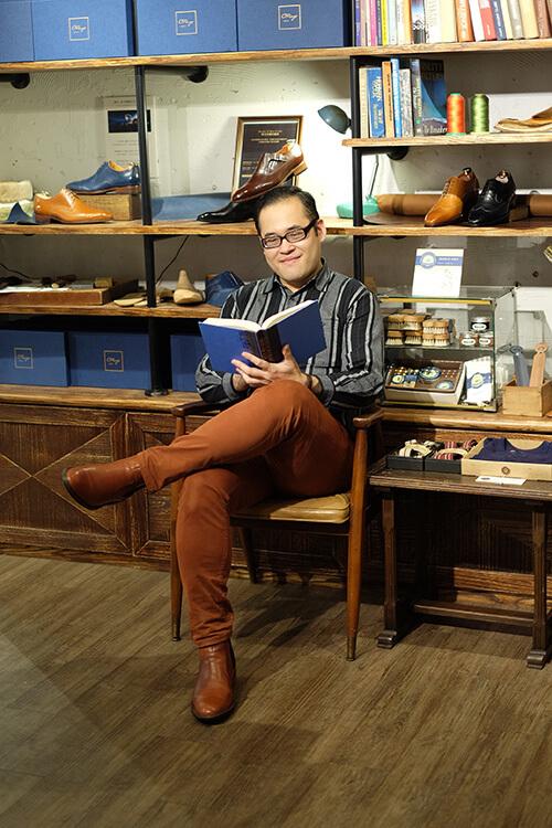 林果客人李寬敏穿著橘色褲子與靴子翹腳坐著看書