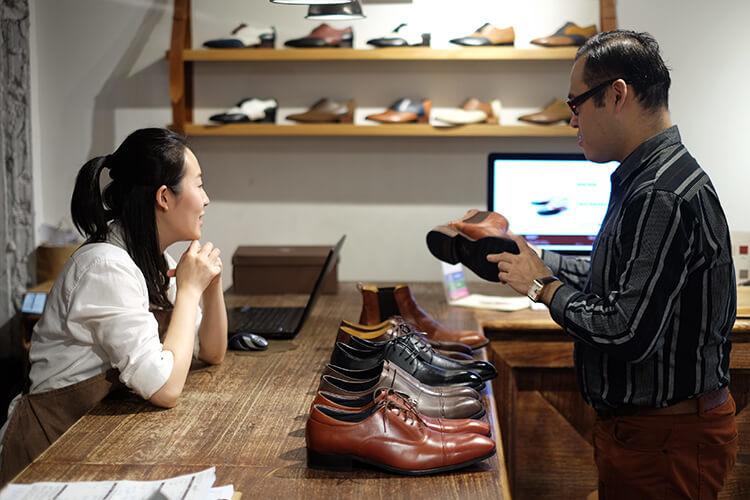 林果夥伴虹臻與客人李寬敏在櫃檯前討論桌上的紳仕鞋款