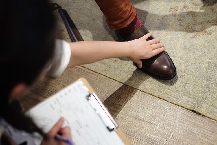 一名女生在碰觸對方的皮鞋並書寫