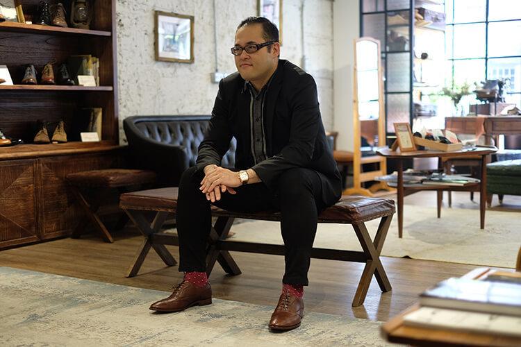 林果客人李寬敏穿黑西裝與咖色牛津鞋坐著