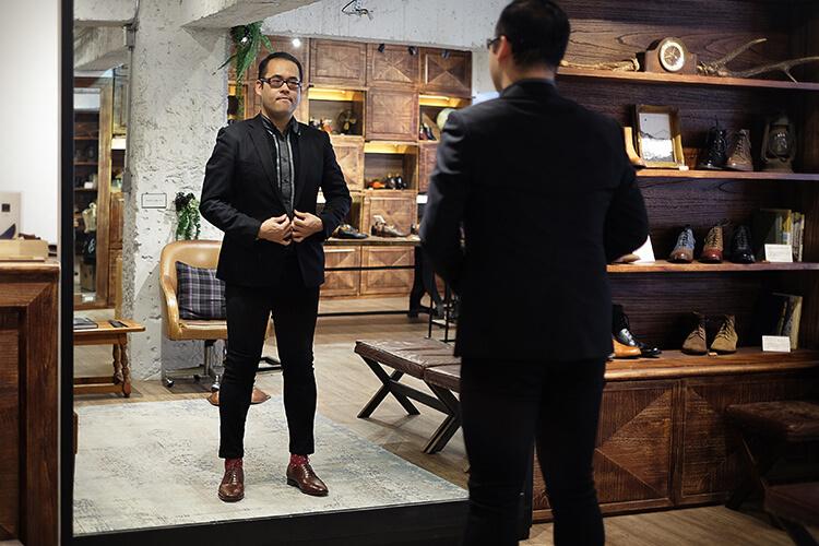 林果客人李寬敏穿黑西裝與牛津鞋在照鏡子