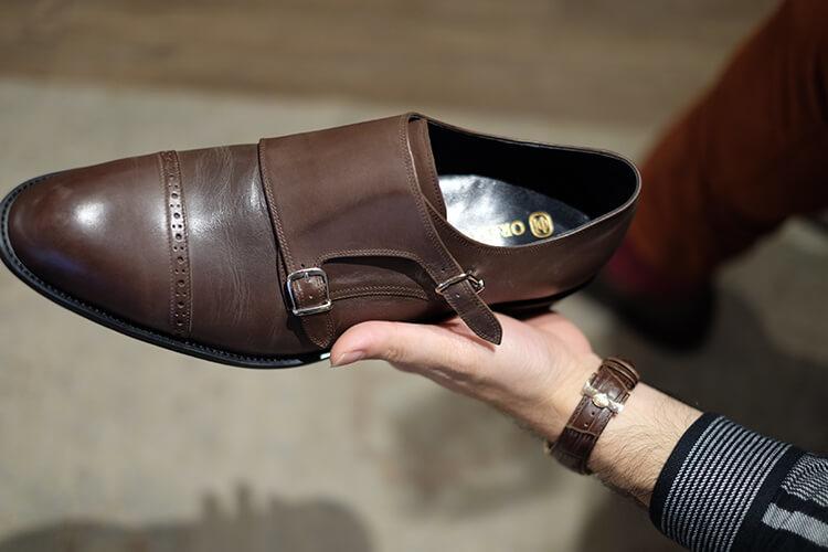 手拿著咖啡色雙釦孟克鞋