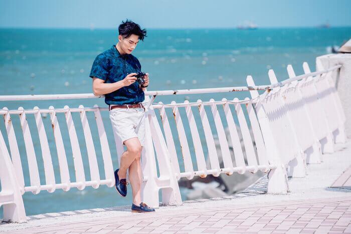 藍色花襯衫搭配白色短褲與帆船鞋的男人靠著欄杆