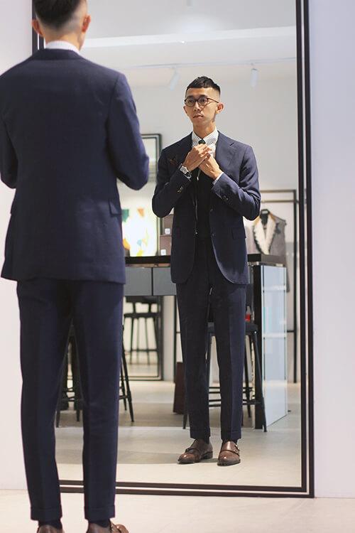 GAUTE台北店店長Brad穿灰西裝照鏡子