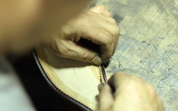 台灣師傅在大底四周貼上延條-台灣製造皮鞋