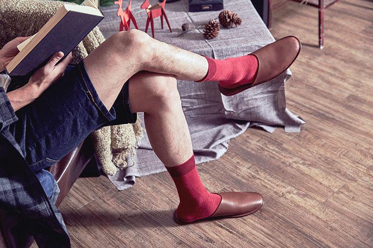 穿著單寧短褲與紅色襪子與室內拖鞋正在閱讀的男人