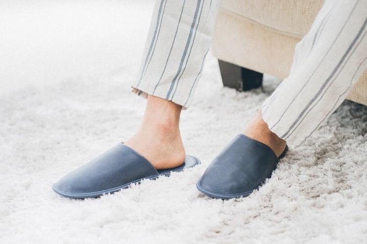 穿著白底藍色條紋褲與室內拖踩在地毯上的人