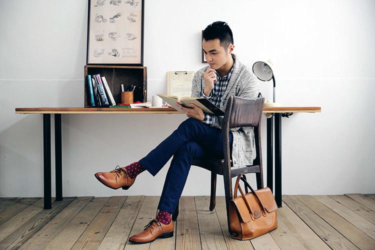 穿著針織外套與格紋襯衫與德比鞋皮鞋正在閱讀的男人