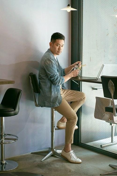 穿著單寧外套與卡其褲與白色皮鞋正在打電腦的男人
