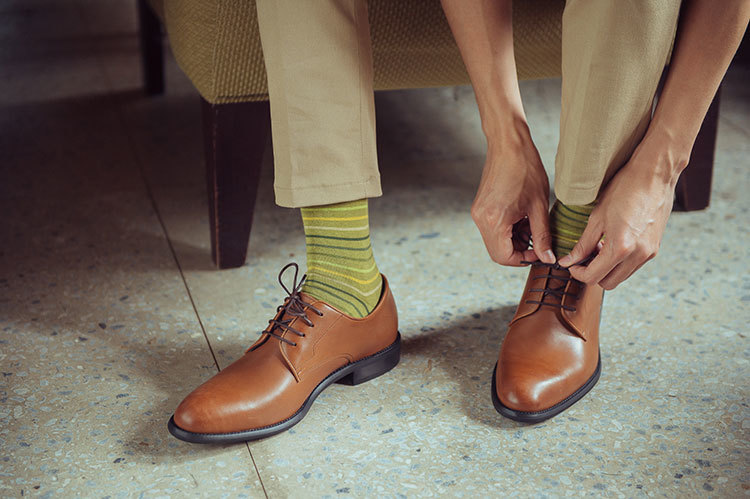 穿著卡其褲與條紋襪與德比鞋皮鞋正在綁鞋帶的男人