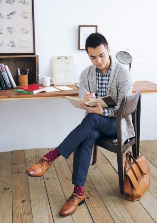 穿著針織外套與格紋襯衫與德比鞋皮鞋正在做筆記的男人