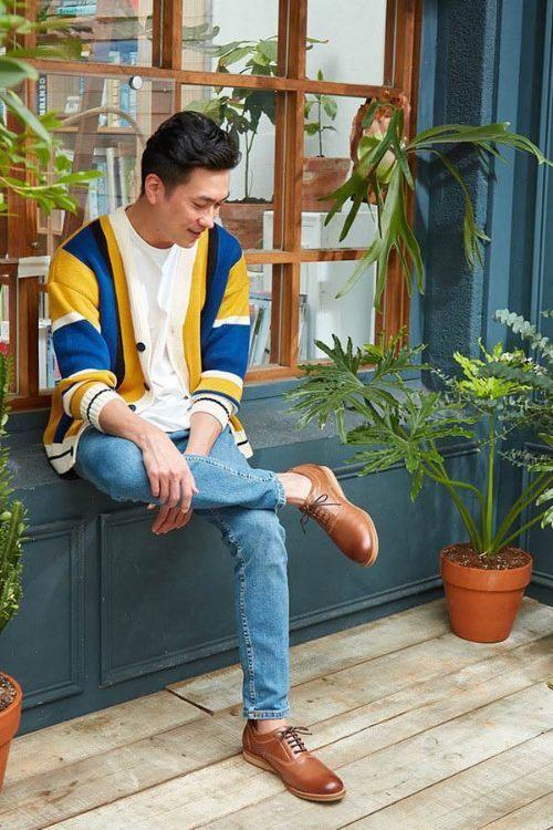 穿著藍黃色外套與白踢與牛津皮鞋正在坐著的男人