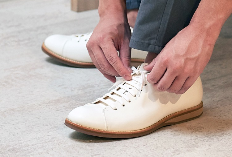 穿著白色皮鞋正在綁鞋帶的人